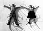 The World of Charles and Ray Eames. Charles and Ray Eames posing with chair bases © Eames Office LLC